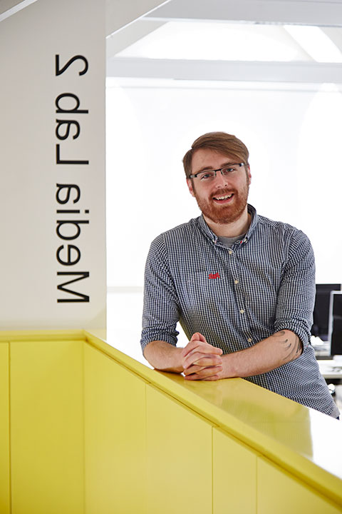 portrait photo of lecturer george beard with hands crossed and leaning on yellow short wall with swept red hair and black framed glasses and a black 和 white plaid shirt