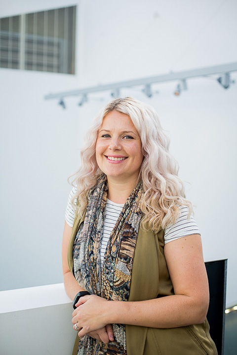 portrait photo of lecturer amy muddle standing with hands crossed and leaning on short white wall and smiling at camera with long light blonde hair and complex patterned scarf 和 a green sleeveless jacket