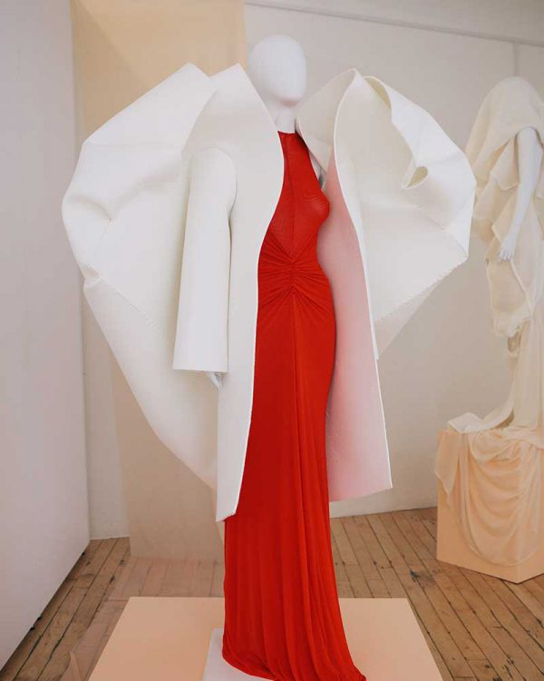Amy Ollett - Image of a mannequin wearing a red dress and a white coat