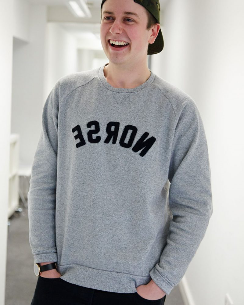 portrait photo of alum 罗斯hawkin smiling away from camera wearing backwards cap and loose tight knit jumper