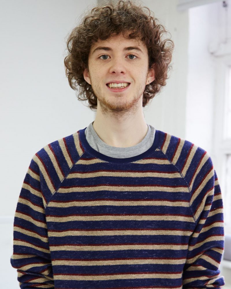portrait photo of alum 迈克尔·巴特利 smiling at camera with curly hair and blue and yellow STriped jumper