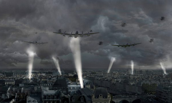 Joshua Garner - computer generated image shows expansive grey city with spotlights shining into the clouds and large bomber planes flying over