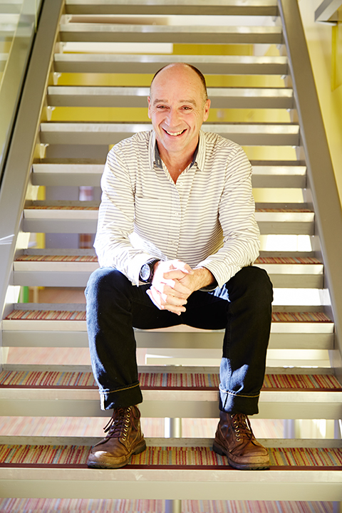 photo of course leader peter martin sitting on stairs and looking at camera while smiling and clutching hands with short hair 和 horizontal striped shirt