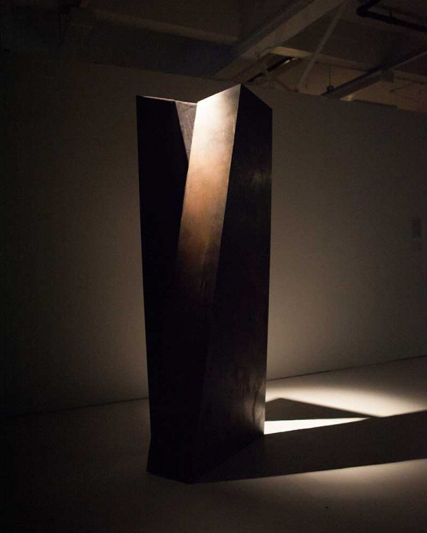 Chrissy Leech - Image of bronze tall sculpture lit by a lamp above it in a fine art studio space at NUA