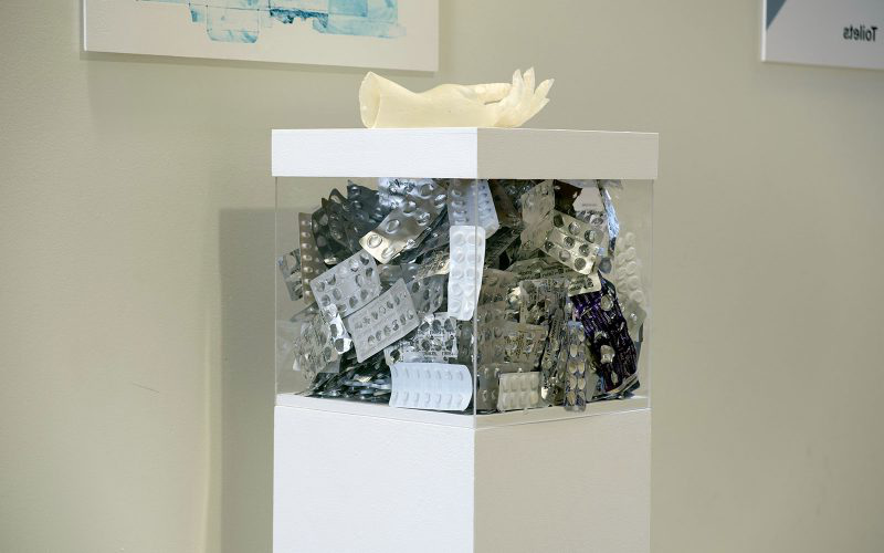 MA Fine Art work by Sarah James showing a glass box full of empty medicine packets with a hand on top in the 硕士学位秀