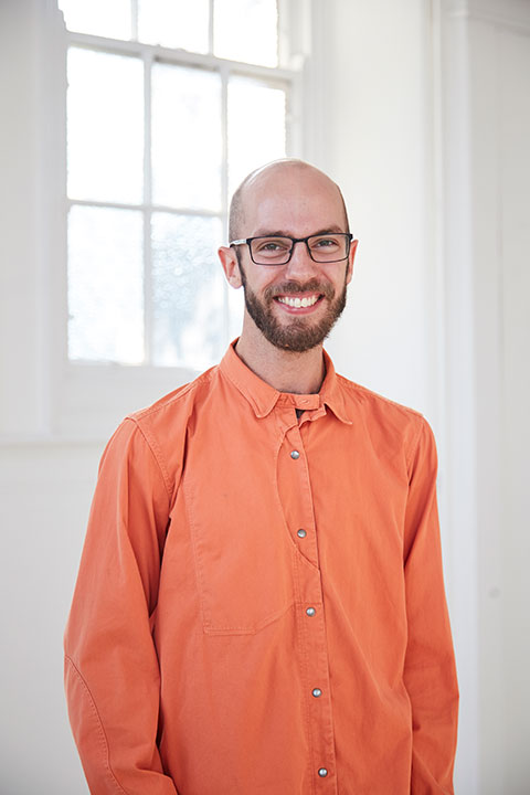 portrait photo of lecturer 马修benington standing with arms at side and smiling at camera with short brown hair with black square framed glasses 和 wearing an orange long sleeved loose shirt