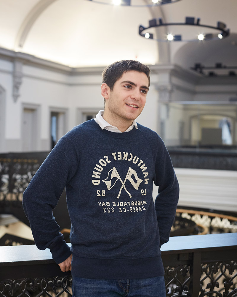 photo of alum Tom Cassidy leaning against railing in large atrium room looking away from camera with short dark brown hair and a dark blue long sleeved jumper
