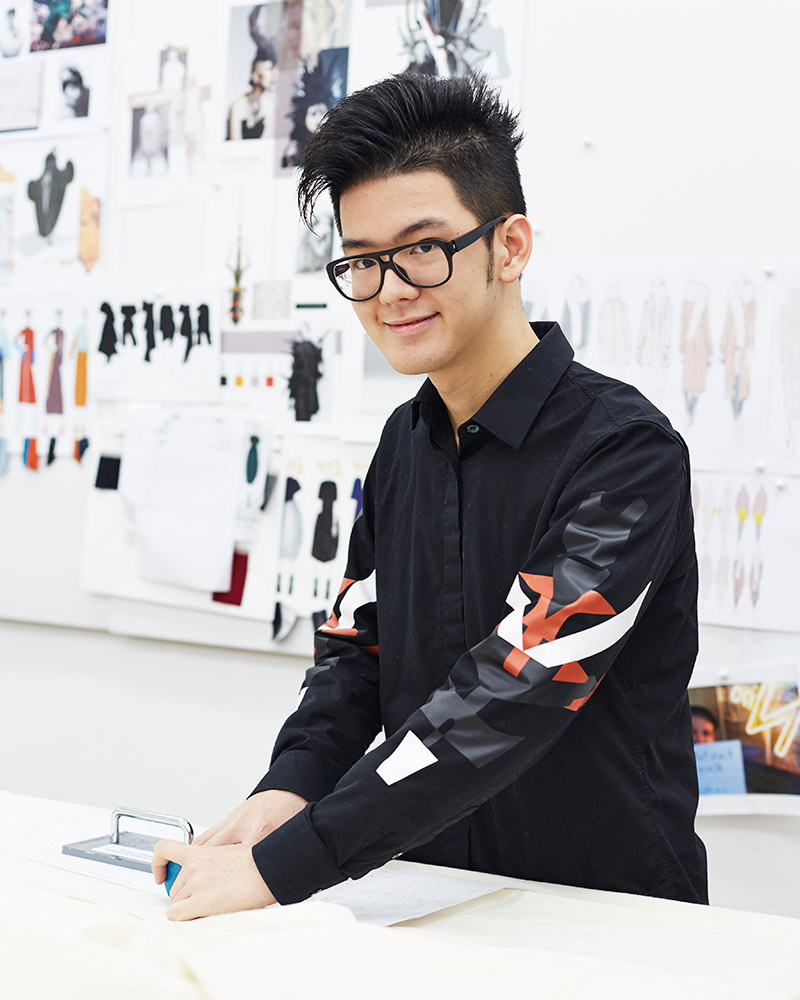 photo of alum 杰里黄 standing at design desk and smiling at camera with hands on fabric material and spiked black hair and thick black glasses and black long sleeved buttoned shirt in a room with a large board on the wall covered with design work