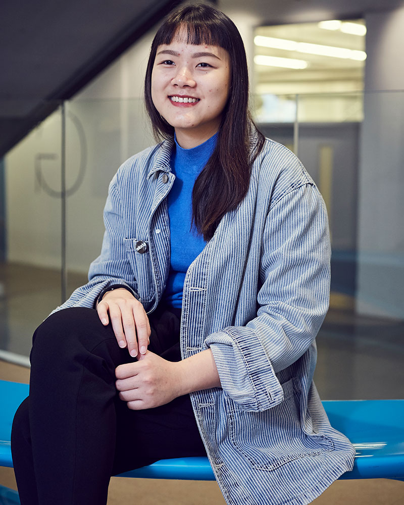 photo of alum TSU-安弘 sitting on a blue bench and smiling while looking away from camera with long black hair and long blue and white vertically striped shirt with a short glass wall in the background