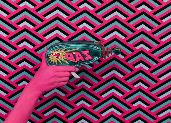 Roxi Lola McCormick-Thompson - Image of a pink patterned background with a pink hand holding a lazer gun with the words ZAP written on