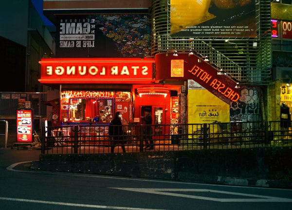 Jason Cleaver - Image of a busy city street in Tokyo with shops with bright neon lights