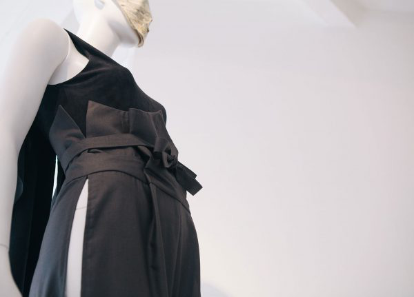 Uzair Khan - Image of the detail of a tailored garment featuring grey trousers and a black top