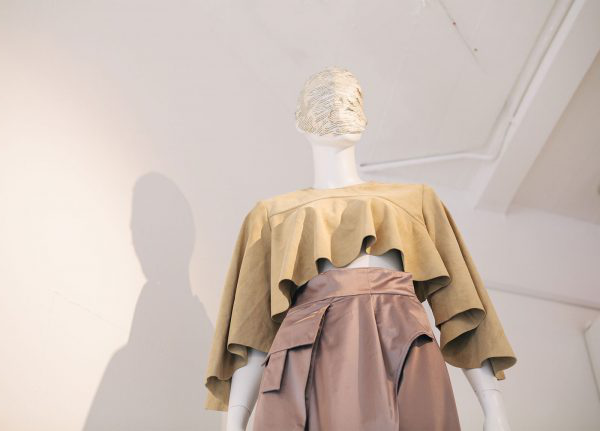 Uzair Khan - Image of a mannequin draped in a yellow garment wearing pink trousers