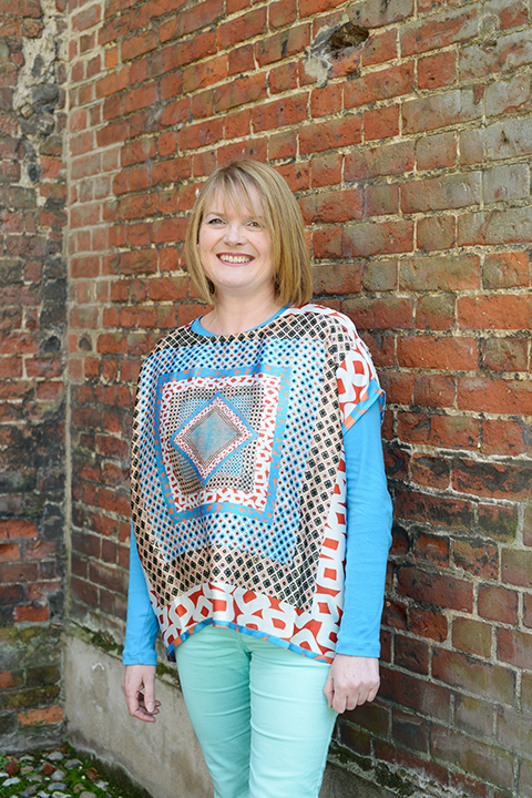 portrait photo of senior lecturer lucy blazey standing with arms by side and smiling at camera with medium blonde hair and a top with multiple square patterns reducing in size towards the centre