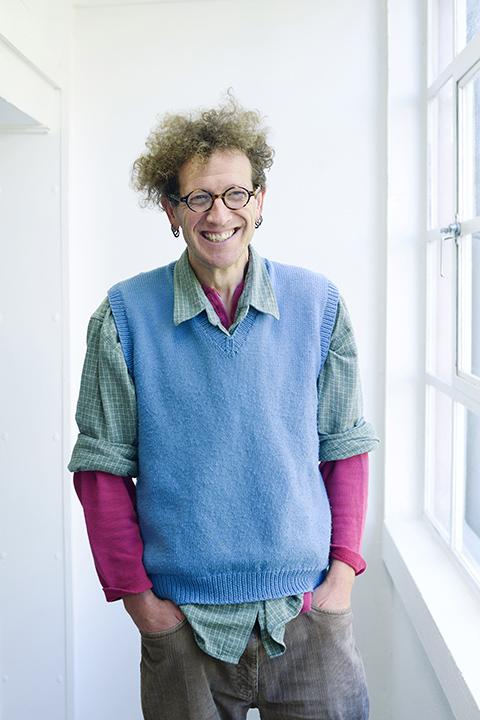 portrait photo of lecturer Nigel Bousfield standing with hands in pockets and smiling at camera with curly blonde hair and round brown glasses with a blue sweatervest and plaid green and white rolled sleeve shirt 和 a long sleeve pink undershirt