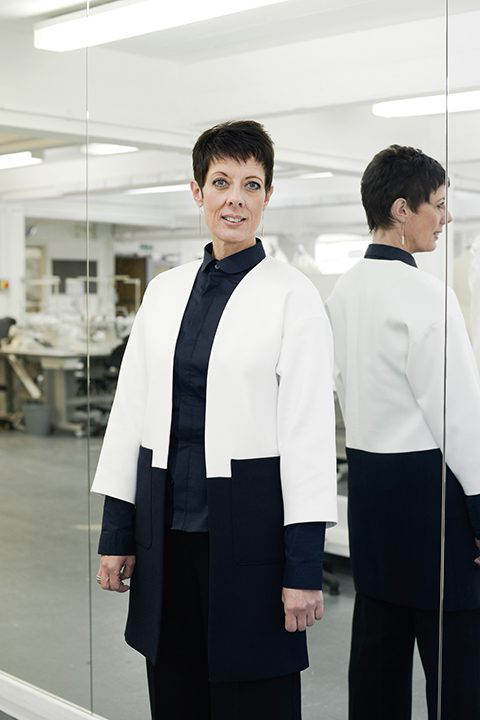 portrait photo of associate professor and course leader 起诉chowles standing next to tall wall of mirrors and smiling whilst looking away from camera with short black hair and a white and blue coat jacket