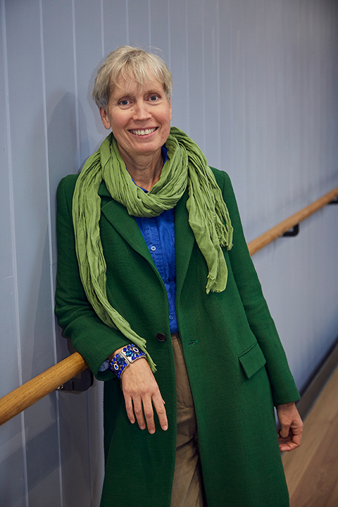 portrait photo of lecturer sharon tolaini-sage leaning against railing and smiling at camera with short blonde hair and a green scarf 和 a long green coat