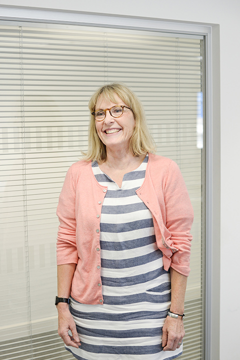 portrait photo of associate lecturer vicki winteringham standing with arms by side and smiling away from camera with medium blonde hair and light brown glasses and a blue and white horizontally striped dress 和 rolled pink cardigan