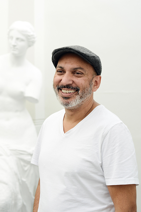 portrait photo of lecturer Suri krishnama smiling and looking away from camera with grey flat cap 和 a white t-shirt