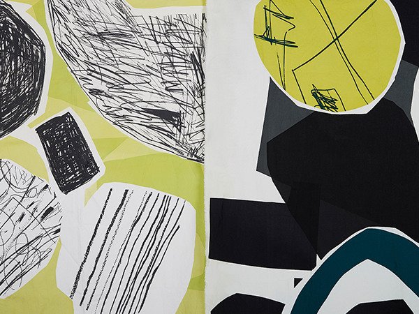 Amelia Elwood - Image of hanging material which has been digitally designed with green, white and black shapes on it