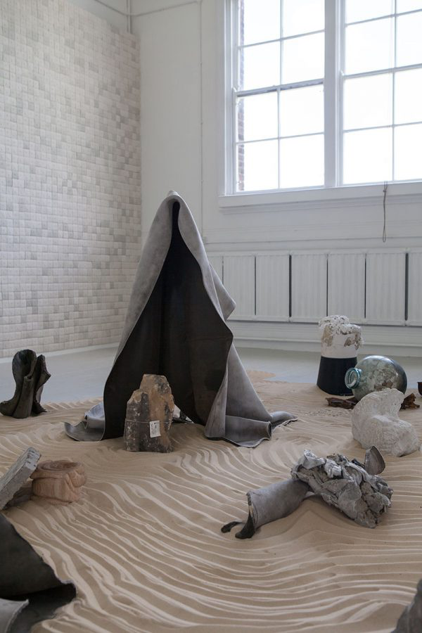 Lindsay Jolly - Fine Art work in the 澳彩网彩票 Degree Show; sand on the floor with objects over it.