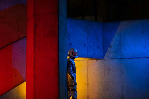 Hannah Gordon-Smith - Image depicts a man in a space suit standing in a concrete scene with red, blue and yellow lights projected onto the space