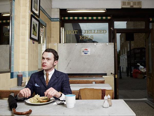 Jamie Garbutt - Image of a man in mod outfit eating in a traditional pie and mash shop