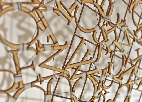 Kirsty Campbell - Image of lasercut wooden letters hanging on a wall, stitched together with tape