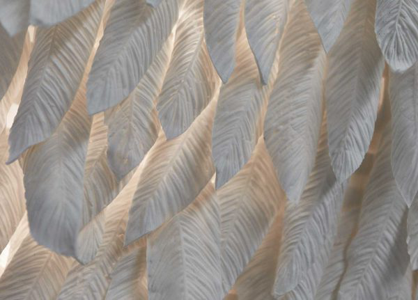 Rachel Harrison - Image of craftred white feathers arranged in a close close pattern on a wall