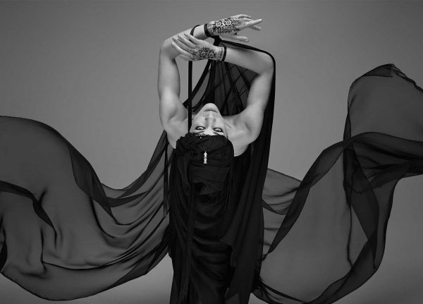 Wadha Alsudairy - Image of a woman leaning towards the camera wearing a floating black drape