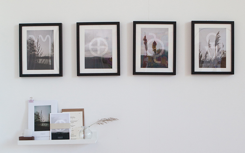 Image of Beth Poulter's work in the BA Degree Show 2018 of four framed photos on the wall and a collection of postcards and posters on a white shelf