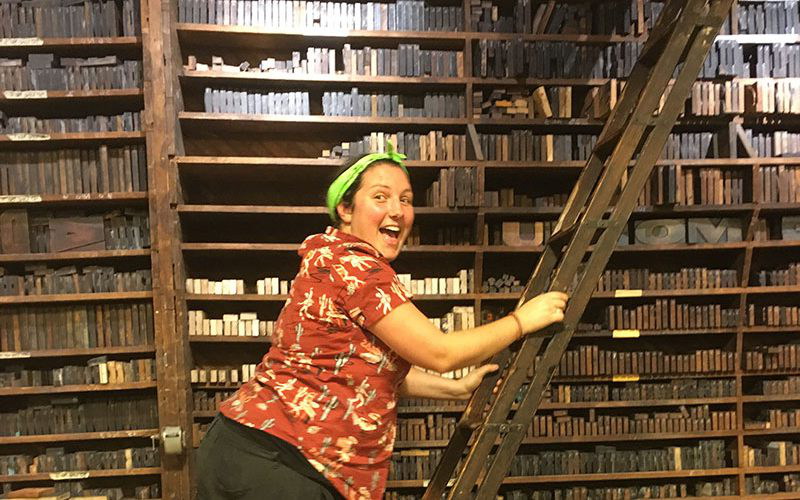 Jo Stafford, Print Technician at 澳彩网彩票 climbs a ladder by a bookcase in a print studio in the US