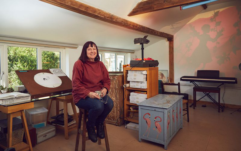 Professor Suzie Hanna, Animation Lecturer at 诺维奇 University of the Arts sits in her home-made studio on a stool.
