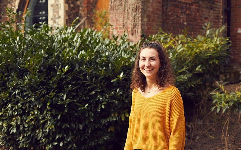 Student Jo Lauren stood in front of a hedge in a yellow jumper