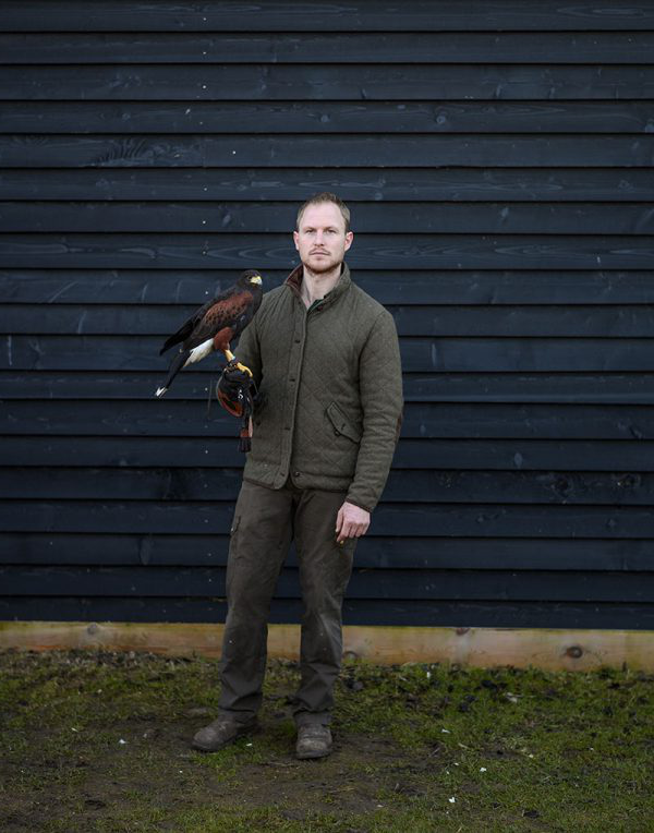 Benjamin Leech - Man standing with a bird of prey on his arm standing next to a blue wall, photo by BA Photography student Benjamin Leach