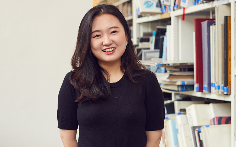 Photo of a young Korean woman smiling and looking at the camera standing in front of a shelf of books
