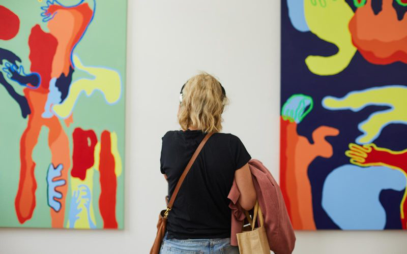 A visitor wears headphones at the 澳彩网彩票 学位节目 and looks at brightly coloured art