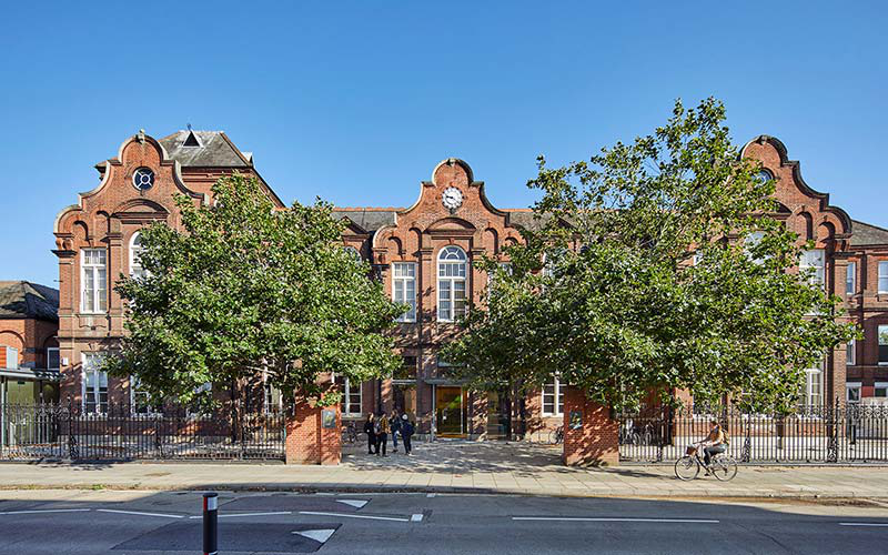 A large red brick building with ornate roof and a clock in the centre against a blue sky with two green trees in front