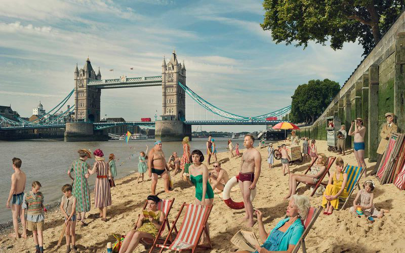 Image of the Thames Beach with Tower Bridge in the background with people playing in the sand and sitting on the beach by Julia Fullerton Batten