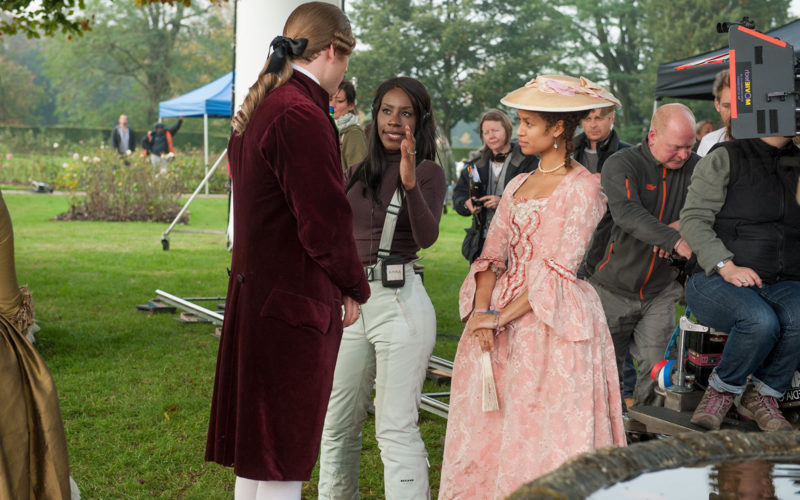 Amma Asante standing on set next to two actors in period outfits