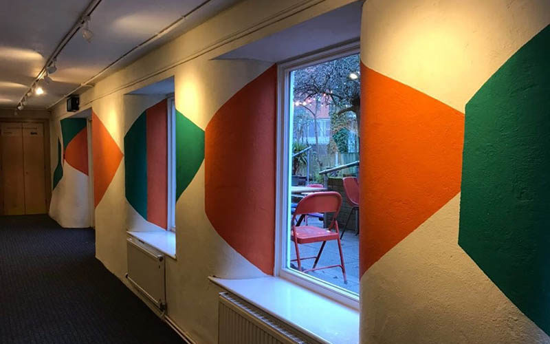 Corridor with dark floor and large windows, with orange, green and pink shapes painted onto the walls