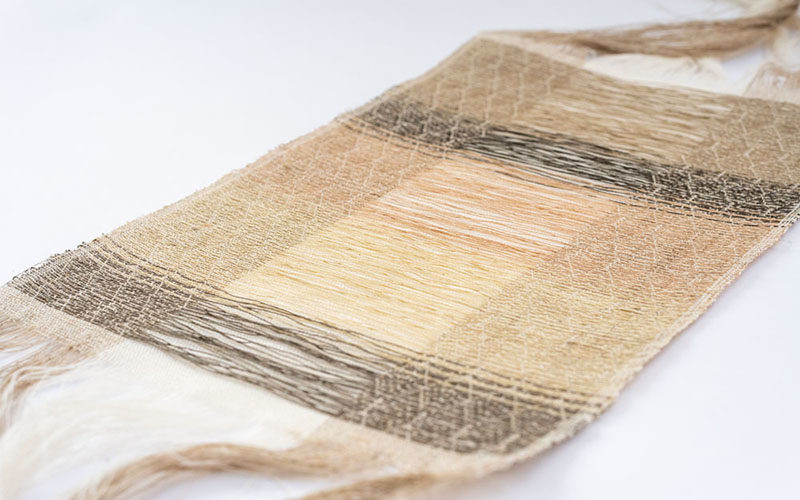 Delicate woven strip of textiles in pale colours laid flat on a white surface