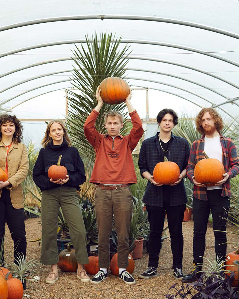 Wild Paths students stand in Urban Jungle Norwich with pumpkins for a Norwich University of the Arts photoshoot