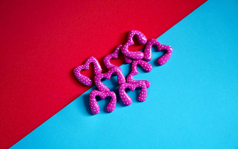 BA Fine Art work by 澳彩网彩票 student Sophie Banks of pink objects shaped like an 'm' called Dave, with white polka dots, on top of a blue and red background