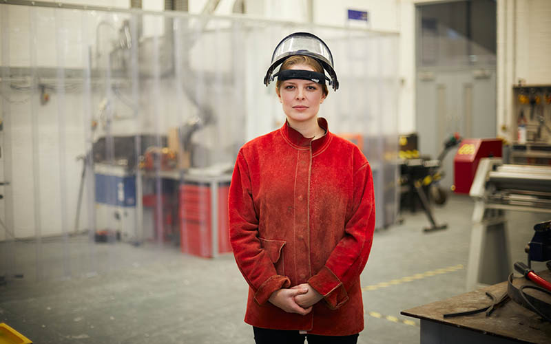 A young woman in a bright red jacket and welding mask on her head stands straight in front of the camera in a workshop