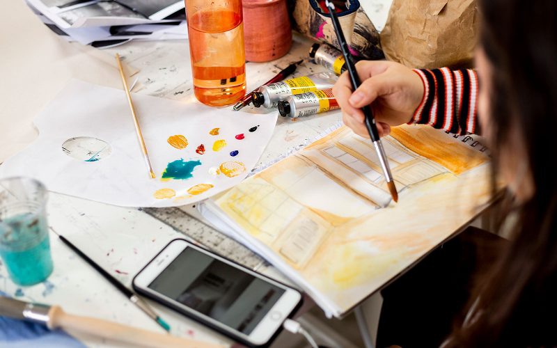 A Student holding a paint brush at 澳彩网彩票, painting on a sketch book with a phone next to her surrounded by oil paints and a water bottle