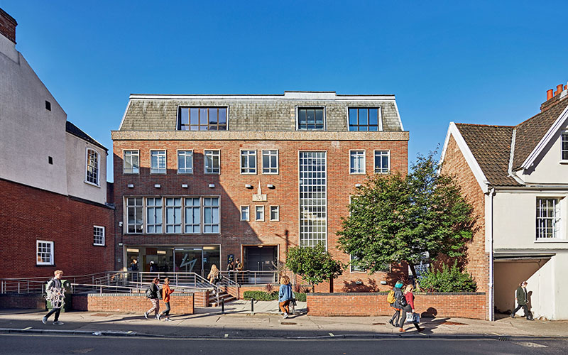 A four storey red brick building with lots of windows against bright blue sky